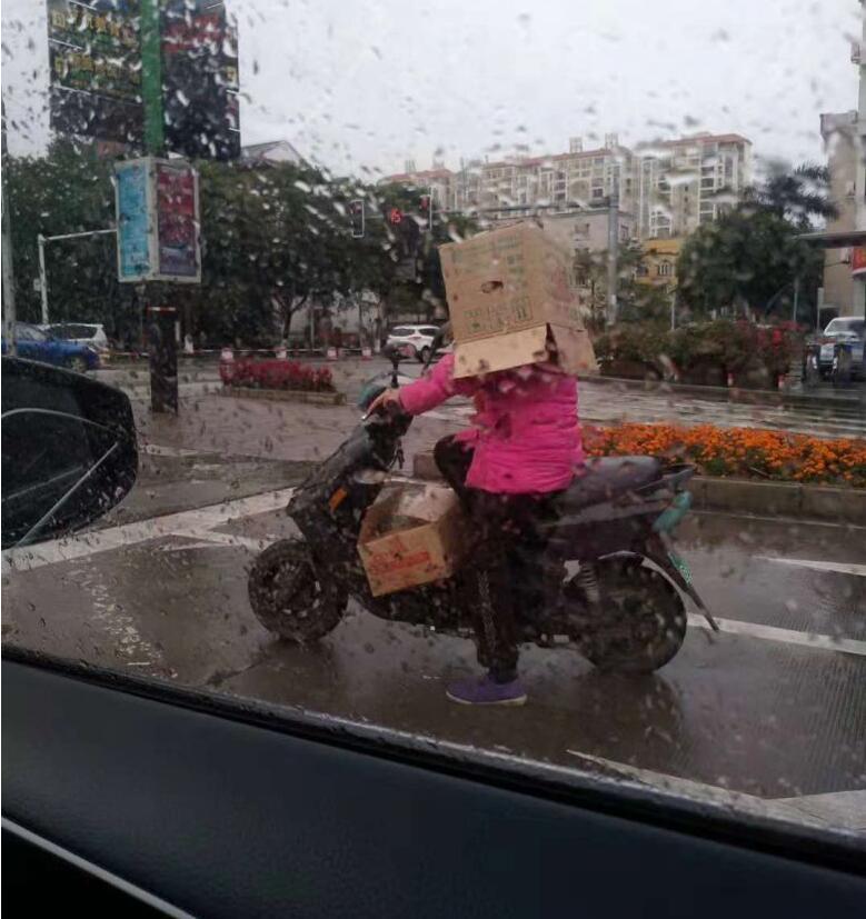 钦州街头危险一幕!头套纸箱当头盔